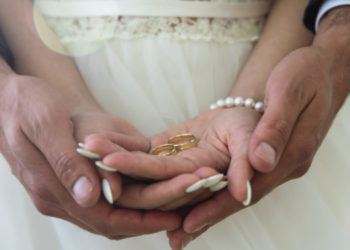 Two golden wedding rings on bride and groom's palms. Wedding rings on the palm